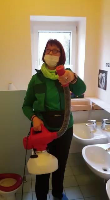 Reinigungskraft desinfiziert Waschraum im Kindergarten
